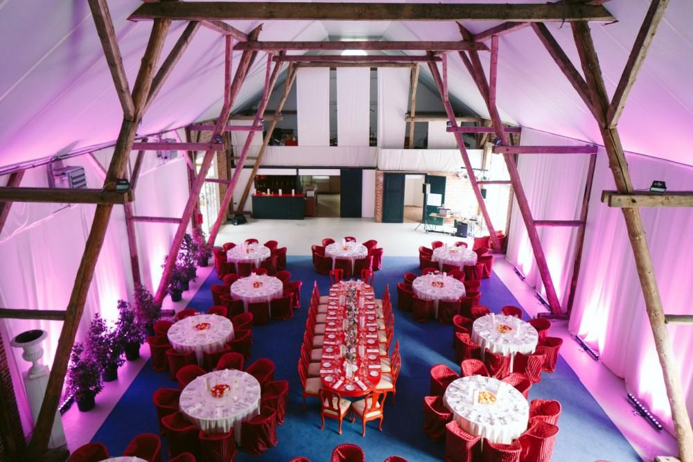 hochzeitsfeier im pinken Raum mit neun tischen mit catering