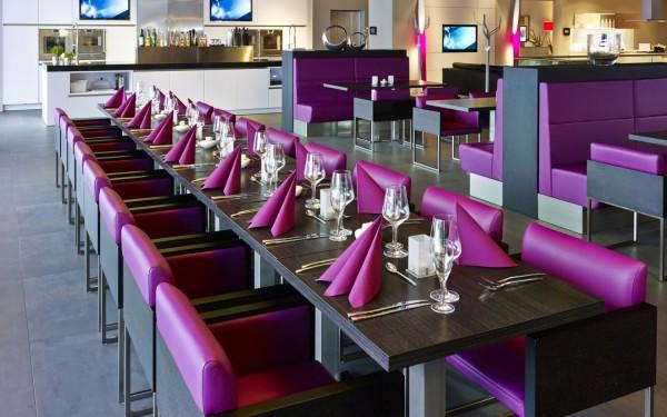 Tisch mit lila servietten, stühlen, gläsern und gewürzen
