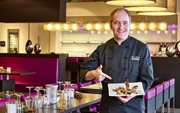 steve zeigt auf einen teller mit essen während er in einer küche steht