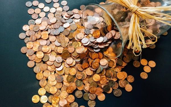 geldmünzen fallen aus einer umgekippten vase