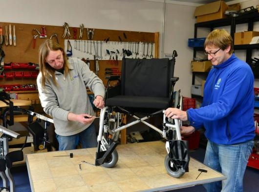 Monteure reparieren einen Rollstuhl, sanitätshaus, sanitäre produkte